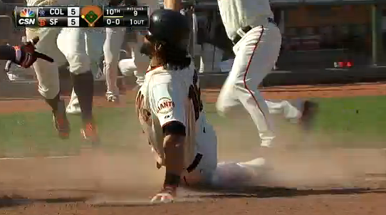 Angel Pagan slides into a jumping gang of San Francisco Giants.